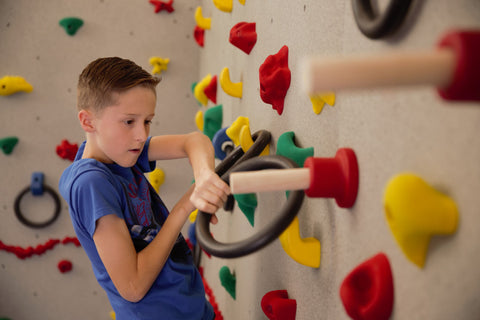 Boy rock climbing using special hand holds to add challenge that require courage