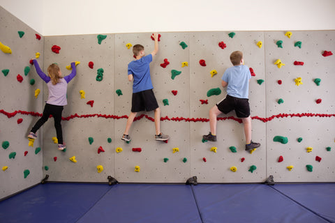 Children rock climbing on a Traverse Wall