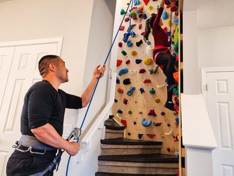 Man and women using home climbing wall