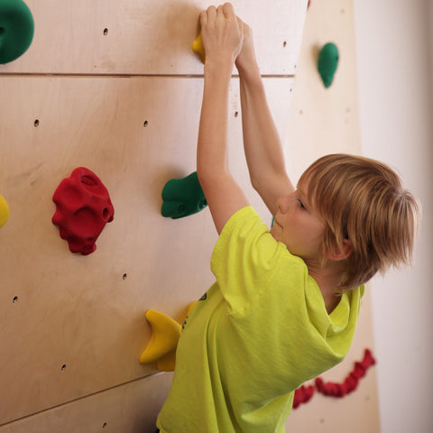 boy rock climbing with hands on the same hand hold
