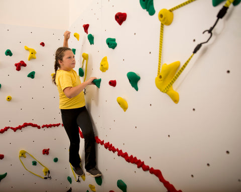 Girl rock climbing while avoiding hand holds that are wrapped with bungee cord