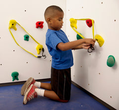 Boy wrapping bungee cords around hand holds to create obstacles on a rock climbing wall