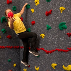 Girl catching red ball while on a rock climbing wall