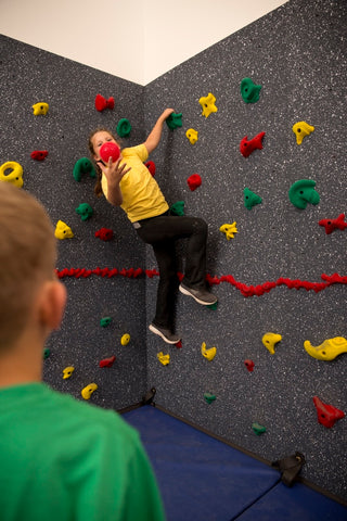 Boy throwing ball to girl on rock climbing wall