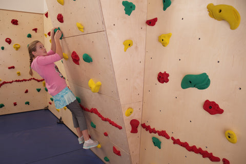 Teenage girl rock climbing on an overhang by Everlast Climbing