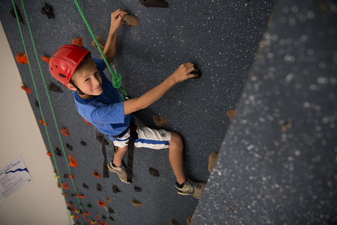 Teenage boy rock climbing on a top rope climbing wall by Everlast Climbing