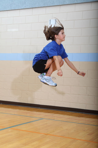 Girl performing tuck jump exercise to build muscular strength