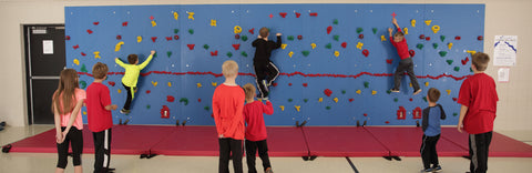Teams of children competing in a relay race on a Traverse Wall.