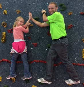 Teacher and Student High-Fiving on Climbing Wall