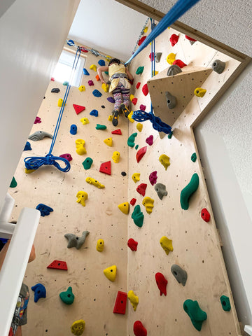 Girl rock climbing on home top rope wall