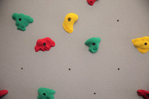 color-coded hand holds on a traverse wall