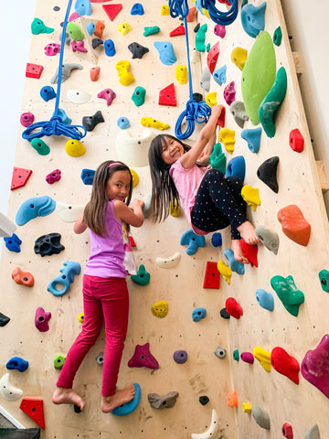 Girls rock climbing on home climbing wall