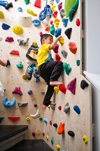Boy rock climbing on home climbing wall