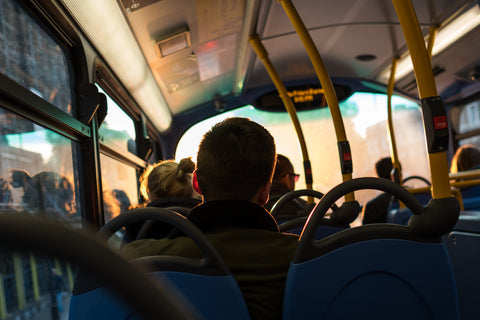 Several people sit on a pubic bus, as viewed from behind.