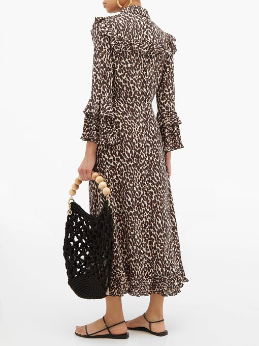 La DoubleJ Long Fancy Dress in Leopard, a full length dress with a slim fit through the shoulders and body and trumpet sleeves available at Debs Boutique. Styled on model back view.