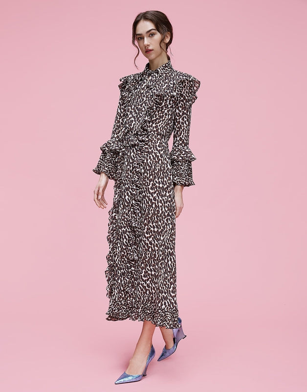 La DoubleJ Long Fancy Dress in Leopard, a full length dress with a slim fit through the shoulders and body and trumpet sleeves available at Debs Boutique. Styled on model with pink background.