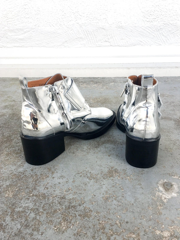 Clergerie Caius Ankle Boots in shiny silver with square toe and buckled straps at Debs Boutique. Back angle view