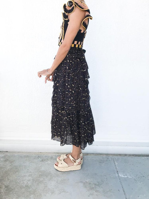 Ulla Johnson Fae Skirt in Jet, feminine silk-cotton-blend midi skirt with lurex stripes with a relaxed fit and fitted waist available at Debs Boutique. Styled on model wearing Ulla Johnson Caia Crochet Top and Clergerie Aude Sandals. Side view.