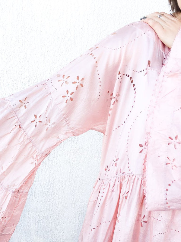Pèro Lasercut silk dress in Pink, with trumpet sleeves, loose fit, dropped shoulders and boat neckline available at Debs Boutique. Styled on model, close up of sleeve details.