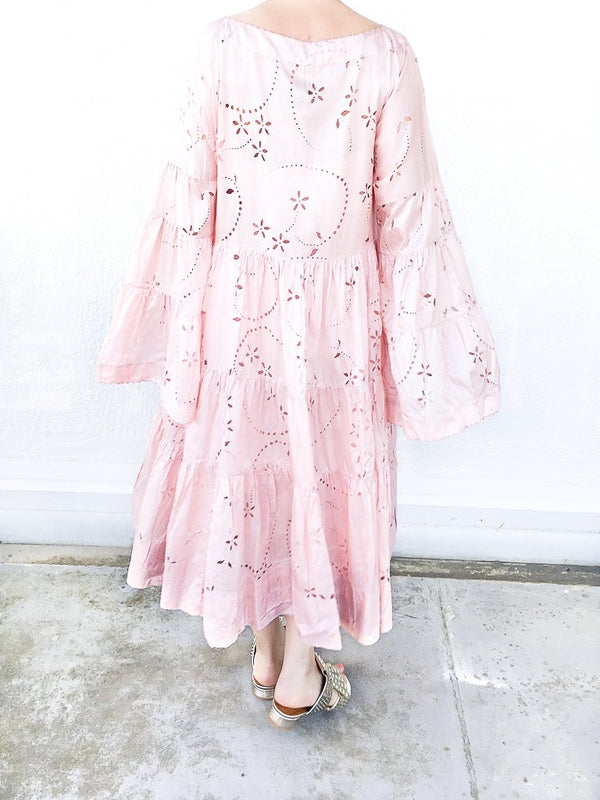 Pèro Lasercut silk dress in Pink, with trumpet sleeves, loose fit, dropped shoulders and boat neckline available at Debs Boutique. Styled on model with Clergerie Figlouc Sandals, back view.
