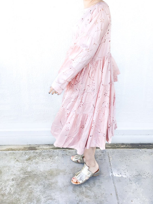 Pèro Lasercut silk dress in Pink, with trumpet sleeves, loose fit, dropped shoulders and boat neckline available at Debs Boutique. Styled on model with Clergerie Figlouc Sandals, side view.