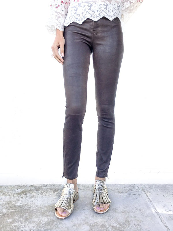 J Brand Mid Rise Skinny Leather Leggings in Dark Brown Sugar in stretch leather with zipper details at the ankles available at Debs Boutique. Styled on model wearing CLERGERIE Cotton Print Tunic and CLERGERIE Figlouc Sandals. Close up view.