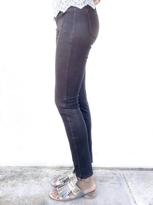 J Brand Mid Rise Skinny Leather Leggings in Dark Brown Sugar in stretch leather with zipper details at the ankles available at Debs Boutique. Styled on model wearing CLERGERIE Cotton Print Tunic and CLERGERIE Figlouc Sandals. Close up side view.