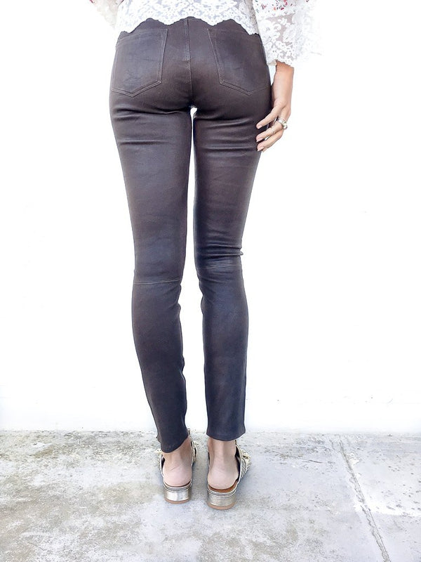 J Brand Mid Rise Skinny Leather Leggings in Dark Brown Sugar in stretch leather with zipper details at the ankles available at Debs Boutique. Styled on model wearing CLERGERIE Cotton Print Tunic and CLERGERIE Figlouc Sandals. Close up back view.