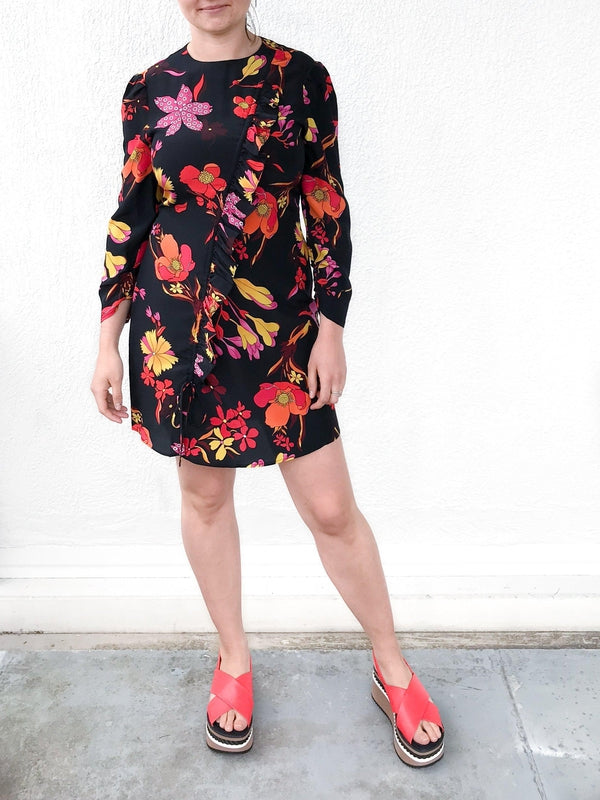 Rixo Gianna Dress in Mixed Disco Floral with front ruffle details and long sleeves available at Debs Boutique. Styled on model wearing Clergerie Omin Platforms. Front view.