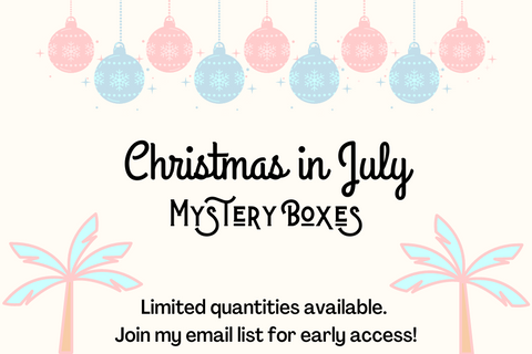 """Pastel colored palm trees and ornaments. Says """"Christmas in July Mystery Boxes. Limited quantities available. Join my list for exclusive early access"""