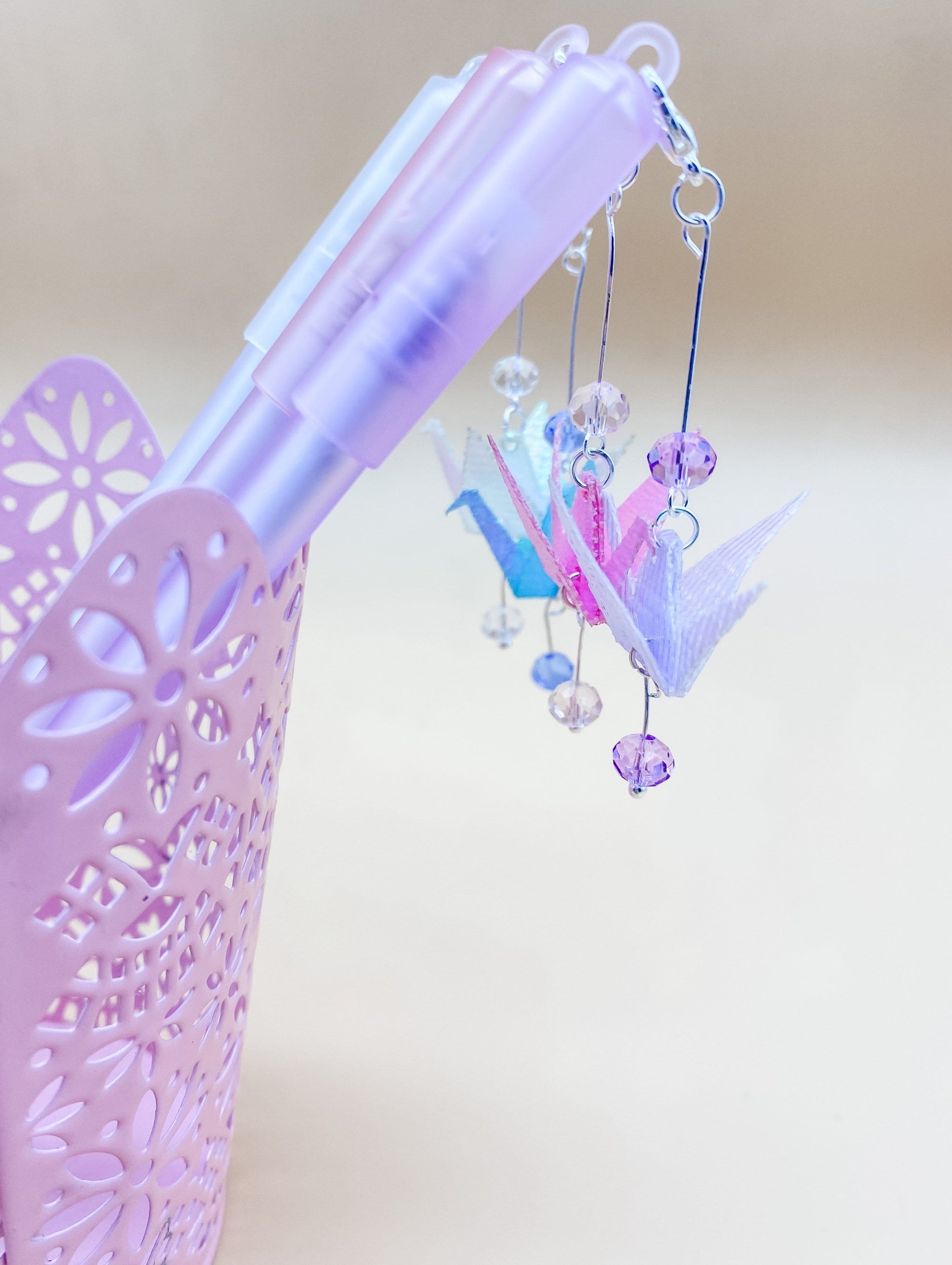 Close up of four pens sitting in a pink metal cup. Only the tops of the pens are visible. They have origami cranes and beads hanging from the caps.