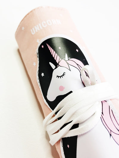 "Close-up of rolled up pencil pouch. It is light pink and has a white unicorn on a black starry background printed on it. It says ""Unicorn"" at the top in all caps. There is a white leather cord wrapped around the pouch."
