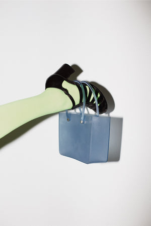 A FOOT HOLDS A BLUE CLEAR BAG