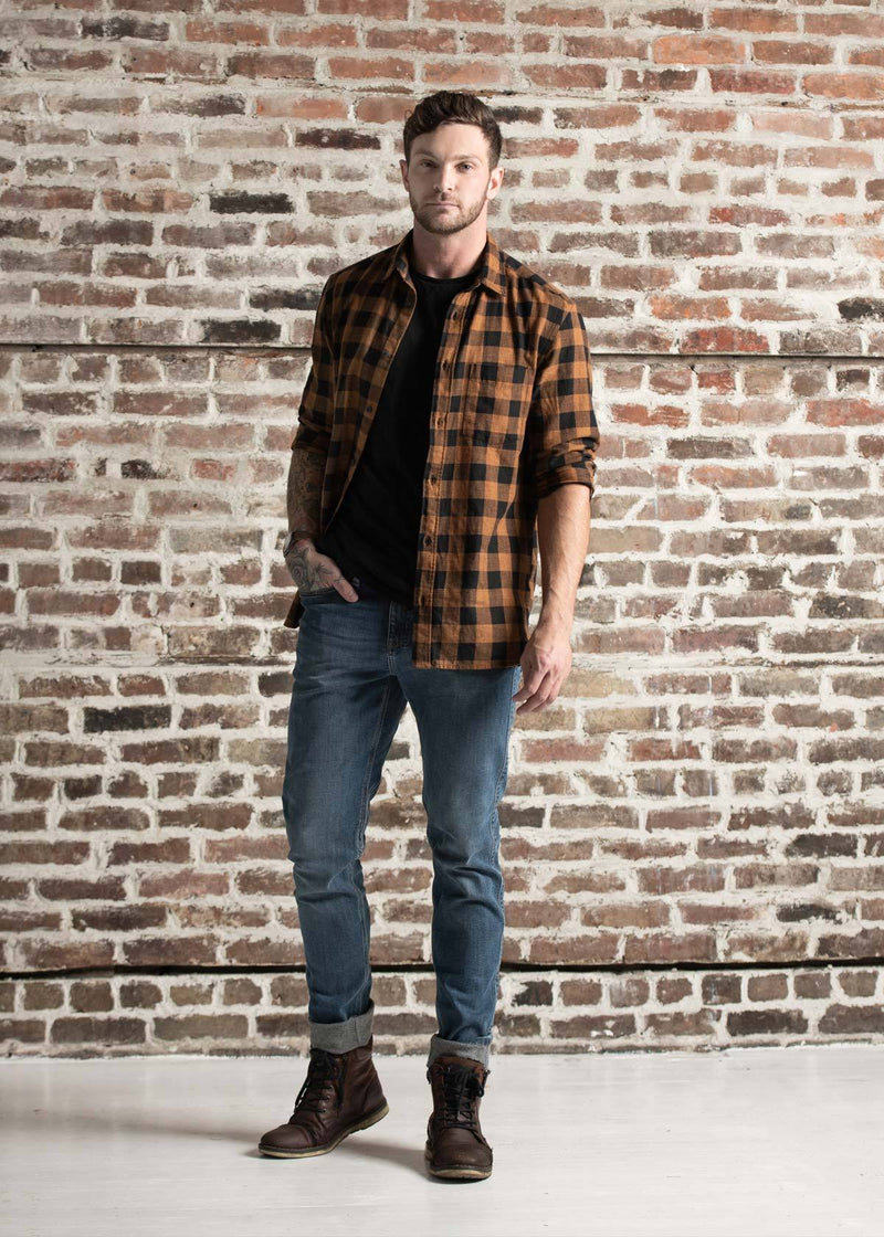 Man wearing blue fleece lined stretch jeans standing in front of brick wall