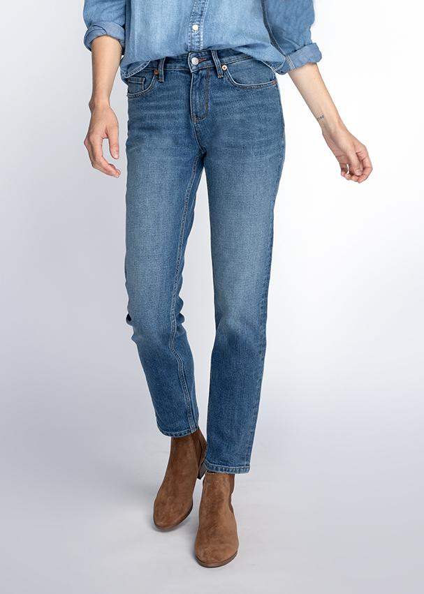Woman wearing blue wash straight leg mid rise stretch jeans backWoman wearing blue wash straight leg mid rise stretch jeans front