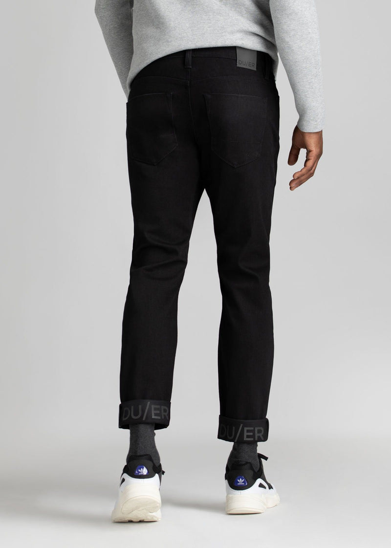 man wearing black slim fit waterproof stretch jeans back
