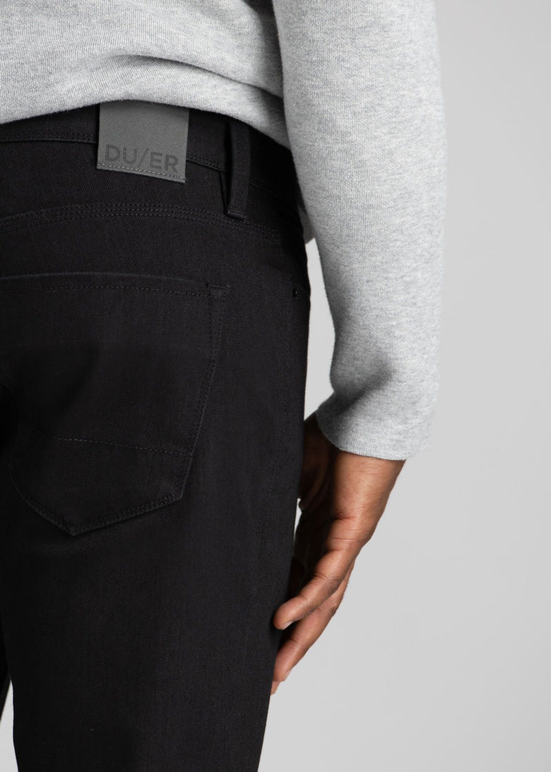 man wearing black slim fit waterproof stretch jeans patch detail