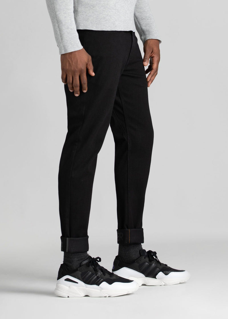man wearing black slim fit waterproof stretch jeans side