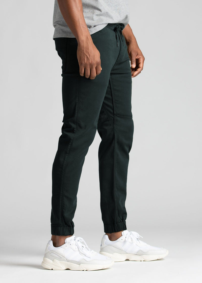 man wearing dark teal athletic joggers side