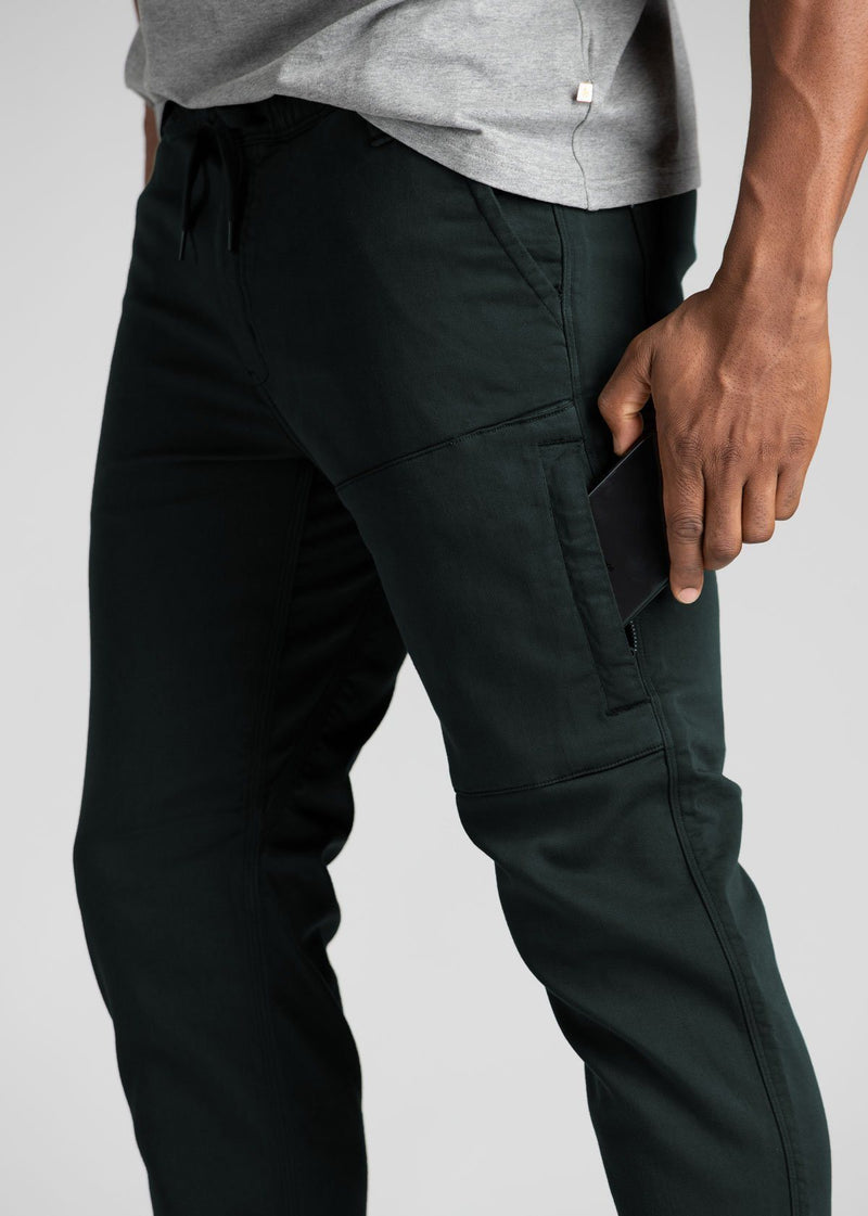 man wearing dark teal athletic joggers side detail