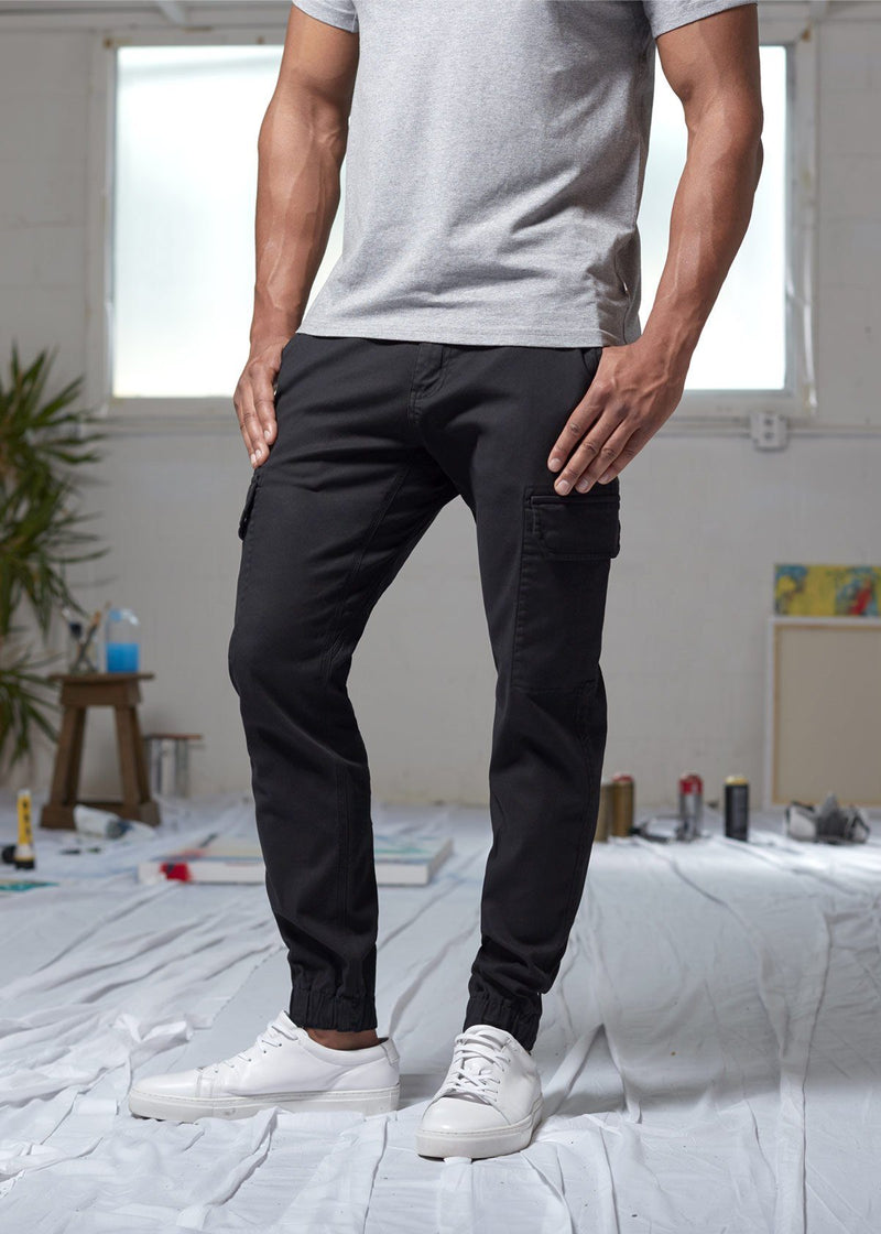 man wearing water resistant black athletic pants slim in art studio