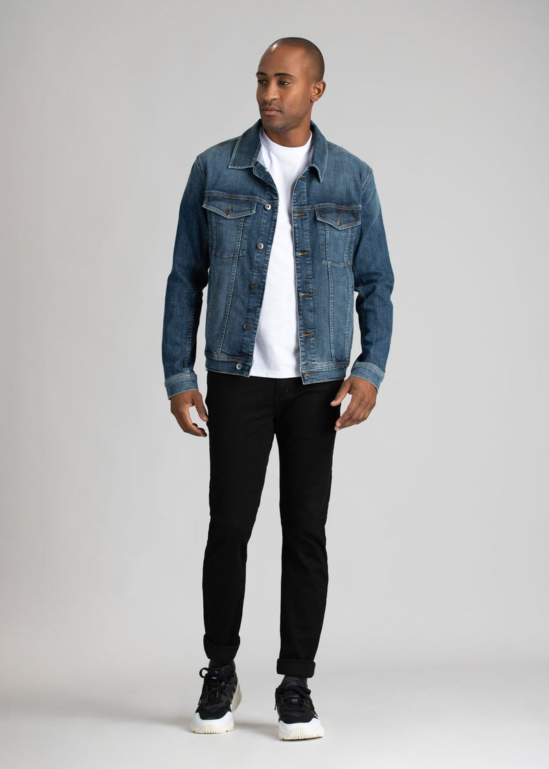 man wearing black water resistant slim jeans with a denim jacket