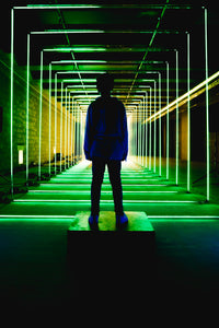 Silhouette of a person by a green light tunnel
