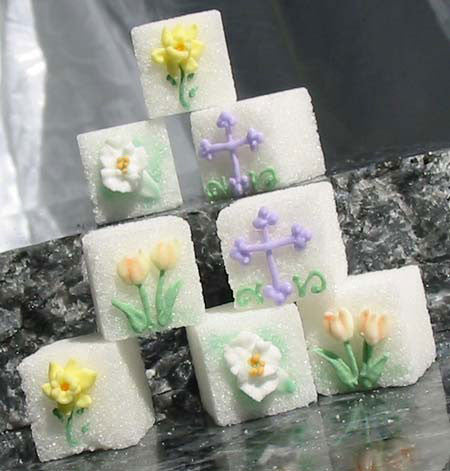 Decorated sugar cubes with spring flowers and a cross