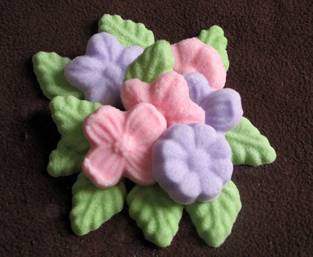 Tea sugars shaped like pink and purple flowers and green leaves