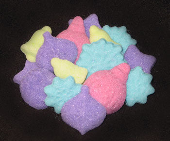 Tea sugars shaped like snowflakes, bells, and ornaments in fuchsia, turquoise, lime, and purple