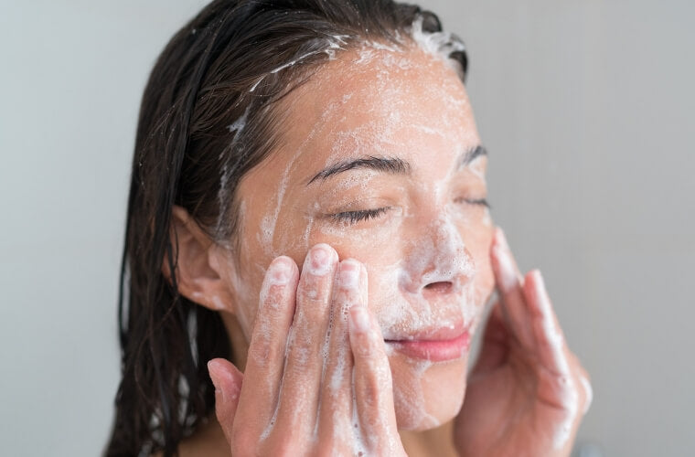 Woman washing face with natural skincare products