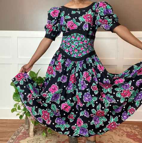 a Black woman in a pink, green, purple and black floral dress with a long, flowing skirt and puffy sleeves. she is holding the skirt spread out with her hands.