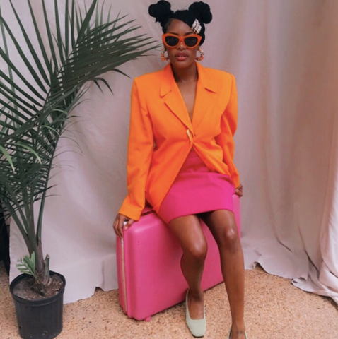Black woman sitting on a bright pink suitcase. she is wearing a bright orangle blazer and bright pink skirt above the knee and pink sunglasses. her hair is in two high buns with a white clip at the front. she is in front of a white curtain, and there is a tall, green potted plant to her left.