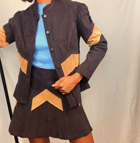 a Black woman stands with her left hand in her pocket. she is wearing a matching skirt and jacket set that is brown with on tan stripe on each piece. she has a baby blue shirt on under the jacket.